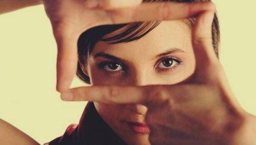 Kontakt wzrokowy - kobieta patrzy przez dłonie