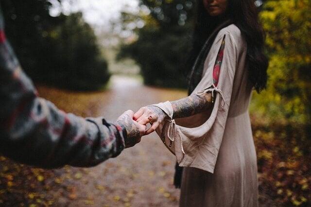 mężczyzna trzymająca za rękę kobietę