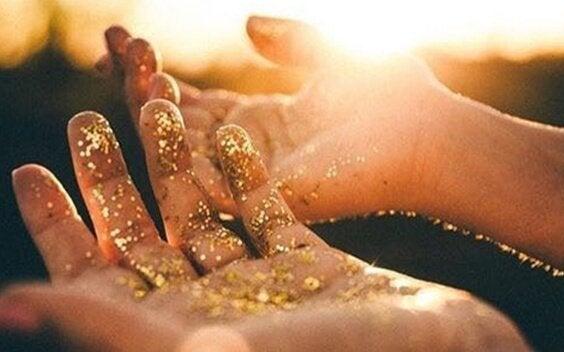 ręce ze złotym pyłem