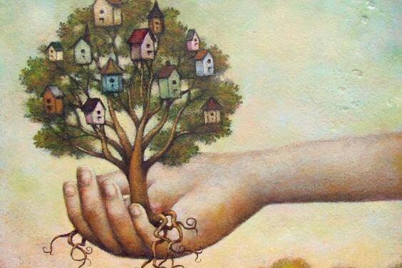 ręka trzymająca drzewo z domami dla ptaków