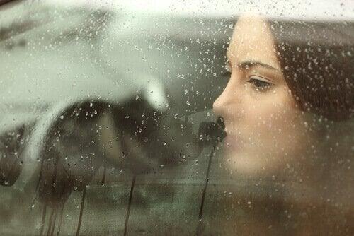 smutna kobieta patrząca przez okno