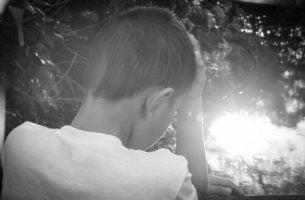 Chłopiec z głową ukrytą w dłoniach - kazirodztwo