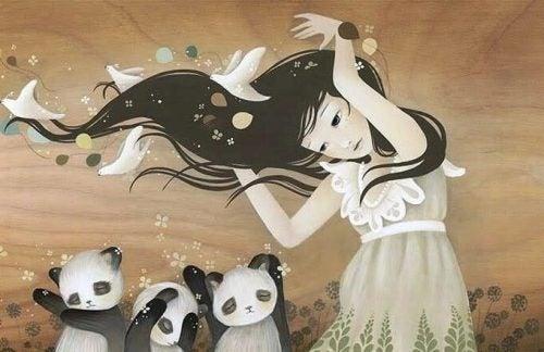 Dziewczyna i trzy pandy stoją na wietrze