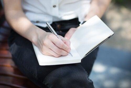 Kobieta pisząca w książce.
