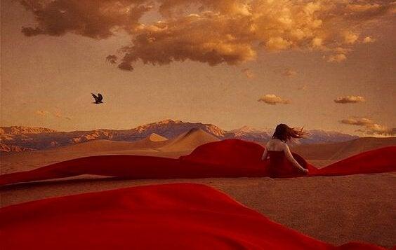 Kobieta siedząca na pustyni.