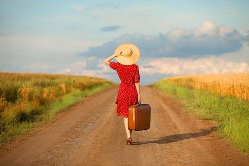 kobieta z walizką na drodze