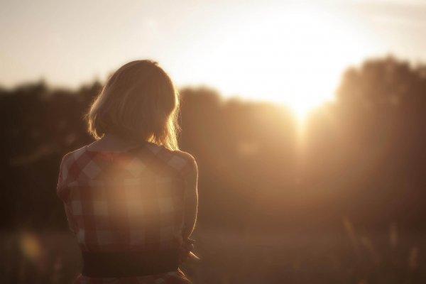 Kobieta kontempluje własny wszechświat o zachodzie słońca