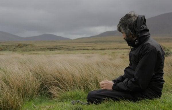 Mężczyzna siedzący na polu.
