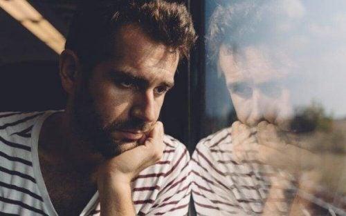 Mężczyzna zamyślony patrzy przez okno - osobowość paranoiczna