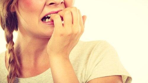 Kobieta obgryzająca paznokcie.
