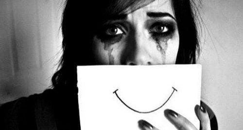 Płacząca kobieta zakrywa twarz kartką z uśmiechem