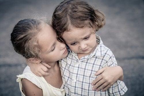 Starsza siostra uspokaja płaczącego brata.