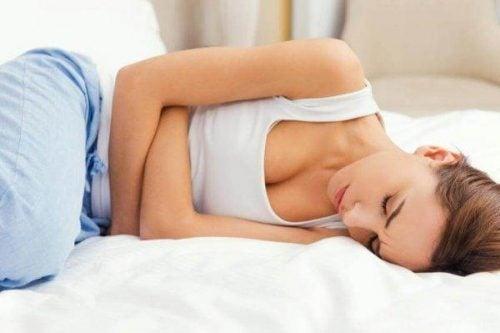 Wpływ stresu na ciało - kobieta leży i cierpi w bólu