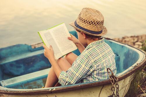 Książki wzmacniające wiarę w siebie u dzieci - Chłopiec czyta w łódce