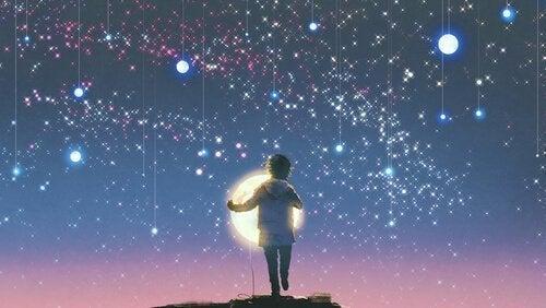Chłopiec na tle księżyca i gwiazd.