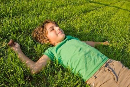 chłopiec leżący na trawie