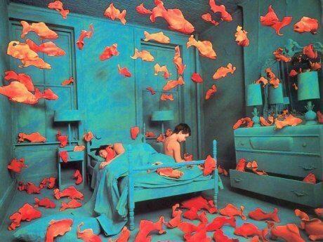 Delirium - człowiek siedzi na łóżku a wokół latają ryby