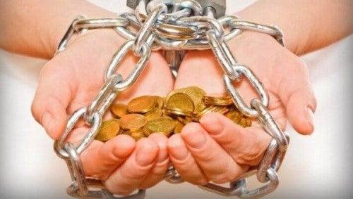 Dłonie z pieniędzmi w kajdankach