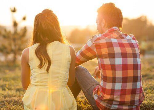 Dwie osoby rozmawiają siedząc na łące