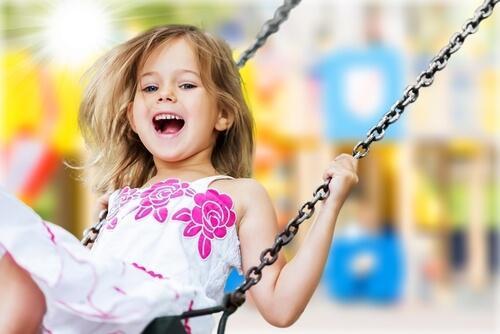 Dzieci, które wierzą w siebie - roześmiana dziewczynka na huśtawce