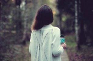 Kobieta na spacerze w lesie.