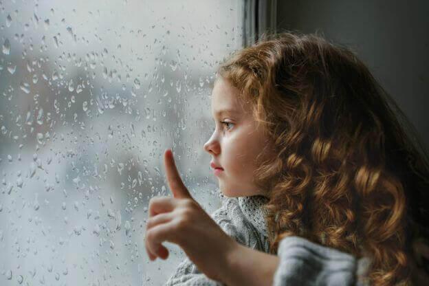 Dziewczynka siedząca przy oknie.