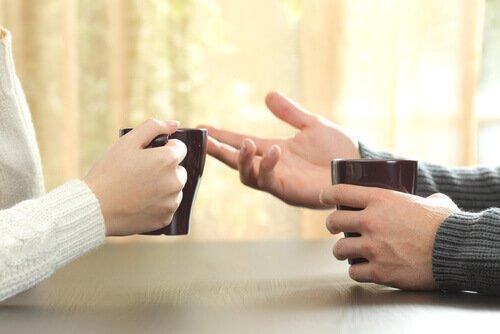 Jak reagować na krytykę - ręce osób rozmawiających przy herbacie