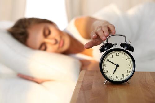 Kobieta wyłączająca budzik.