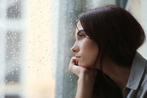Smutna kobieta siedząca przy oknie.