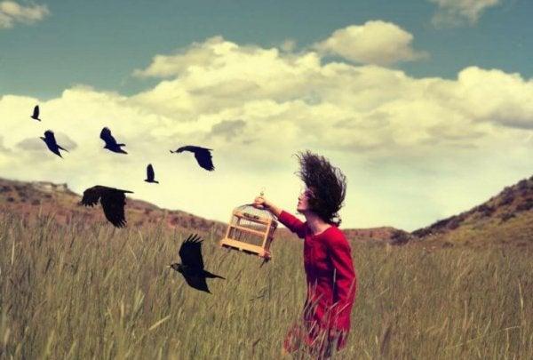 Kobieta wypuszczająca ptaki na wolnośc.
