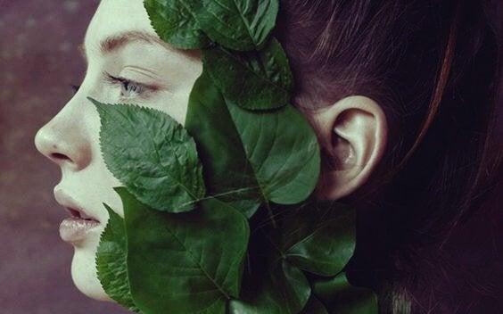 Kobieta z liściami na twarzy.
