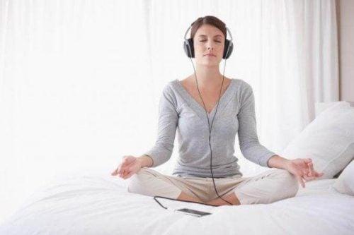 Kobieta słucha muzyki relaksacyjnej w łóżku
