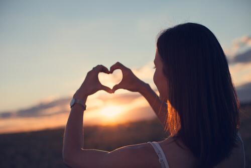 Kobieta tworząca z rąk serce