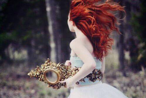 Krytycyzm - kobieta o czerwonych włosach biegnie i trzyma lustro