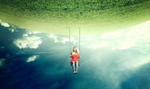 Krytycyzm - kobieta na huśtawce przy odwróconym horyzoncie