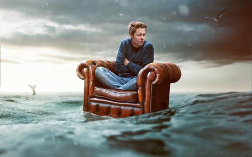 Mężczynza na fotelu na środku morza - fobia społeczna