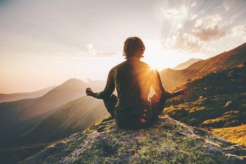 Mężczyzna medytujący w górach.