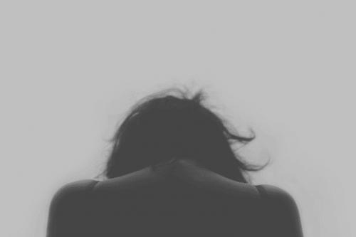 Nadużycia - smutna kobieta patrzy w dół