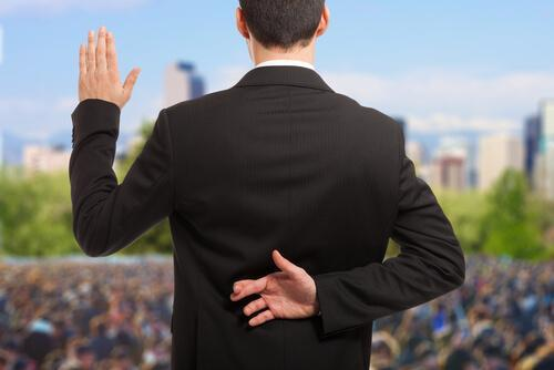 Postprawda - polityk składa przysięgę trzymając za plecami dłoń w geście szczęścia