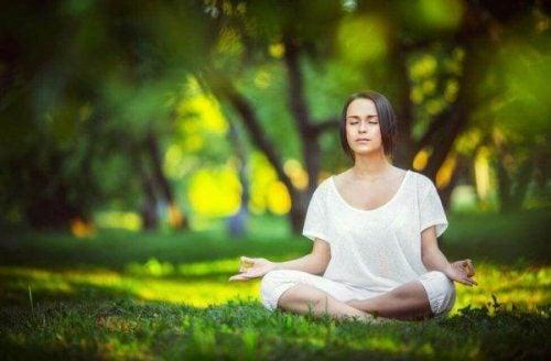 Sofrologia - kobieta medytuje w lesie