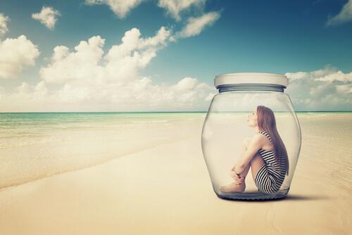 Unikanie doświadczania - kobieta na plaży siedzi zamknięta w szklanym słoiku