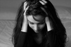Unikanie doświadczania - kobieta trzyma się za głowę