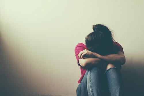 Unikanie doświadczania -smutna kobieta ze schyloną głową