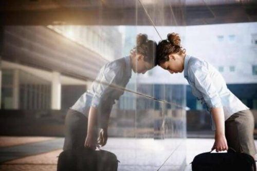 Wykończona kobieta opiera się czołem o ścianę