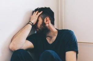 Zażywanie narkotyków - mężczyzna siedzi w kącie pokoju