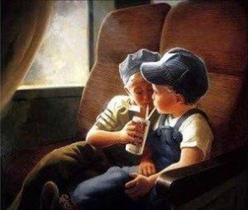 Dwaj chłopcy piją z jednej szklanki