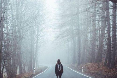 Człowiek idzie drogą we mgle