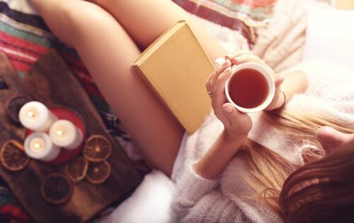 Herbatki relaksacyjne -kobieta pije podczas czytania książki