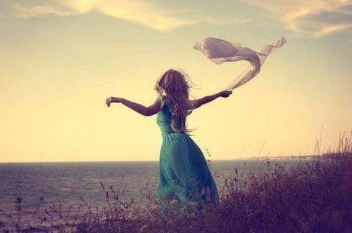 Kobieta z rozwianymi włosami tańczy na polu