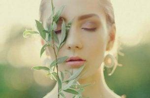 Kobieta z zamkniętymi oczami i kwiatem przy twarzy